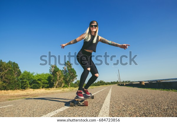 A beautiful, sexy blond hipster with blue hair in a tattoo is riding a longboard.