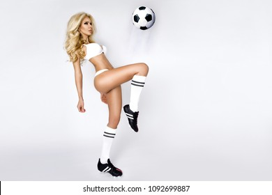 Beautiful, sexy blond woman dressed in sports clothing, playing football.