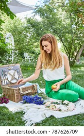 Beautiful sexy blond woman happy life style smile, weekend out for a walk in a picnic park in the summer garden, model sits on plaid basket food outdoor recreation warm summer weather flowers bouquet.