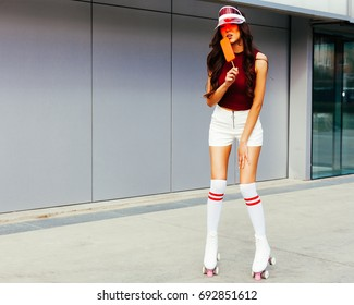 Beautiful sexy blonde asian girl posing on a vintage roller skates in white shorts and red T-shirt on a warm summer evening. Rollers quads derby, enjoyed by ice cream. Outdoor.