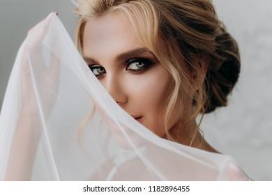 beautiful sexy blonde bride. posing in wedding dress in white room