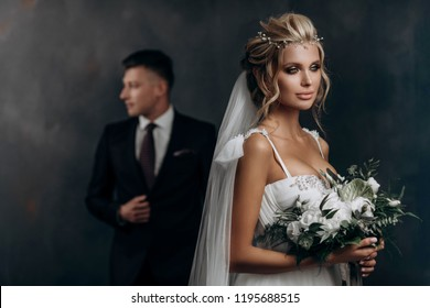 beautiful sexy blonde bride posing in wedding dress with her husband