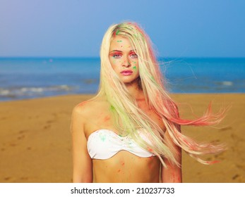 Beautiful sexy blonde in bright Indian colors at the beach