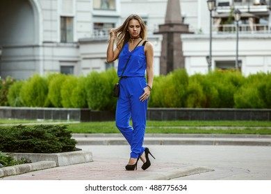 Beautiful sexy blonde business lady in a blue suit walks in the bright, warm town and posing
