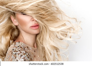 Beautiful sexy blonde female model with amazing long  hair and perfect face posing on a white background