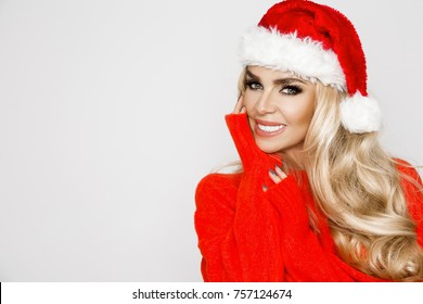 Beautiful sexy blonde female model dressed in a Santa Claus hat. Sensual girl for Christmas.