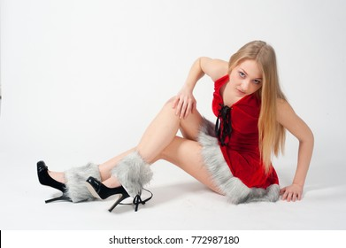 Beautiful sexy blonde female model dressed in a Santa Claus hat and dress. Sensual girl for Christmas