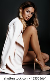 Beautiful, sexy blonde girl with bronze tan in a white coat and beige shoes posing in a studio on a dark background.
