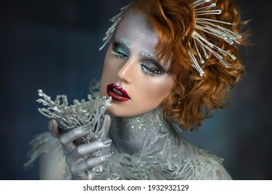 Beautiful sexy blonde girl in jewelry.Ice and fire. The Snow Queen. The gentle girl with winter make-up. Girl with a glass in her hand.Brilliant body.Girl holds a glass in hand