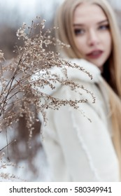 beautiful sexy blonde girl with long hair, full lips in a white coat walking in the winter woods