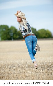 Beautiful sexy blonde girl posing on sloping field