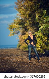 Beautiful sexy blonde girl posing in the autumn leaves