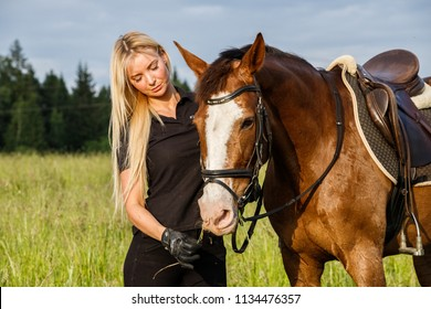 Beautiful sexy blonde girl rides a horse in nature outdoors