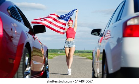 Beautiful sexy blonde girl with a sports figure gives the go-ahead to cars with the American flag, attention to the start. Ready, set, go. Sports cars at the start, speed and excitement. Top gear,