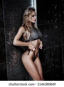 Beautiful sexy blonde girl with wet hair. Posing in a swimsuit in the shower under the drops of water