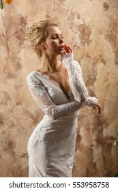 Beautiful sexy blonde girl in white wedding dress posing in a castle near the wall and a Christmas tree