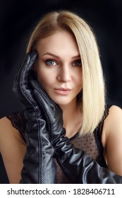 Beautiful sexy blonde in leather gloves on a black background
