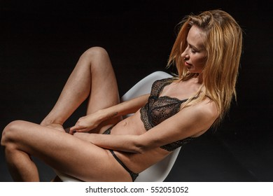 Beautiful sexy blonde in lingerie sits on bar chair and posing on black background
