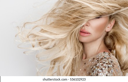 Beautiful sexy blonde model with amazing eyes, wind down long volume hair with highlights, and sensors perfect face dressed in sexy elegant dress