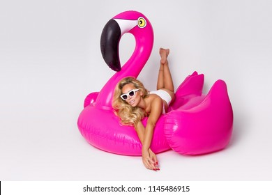 Beautiful, sexy blonde model in a elegant bikini, lies on a pink flamingo. Hit the summer