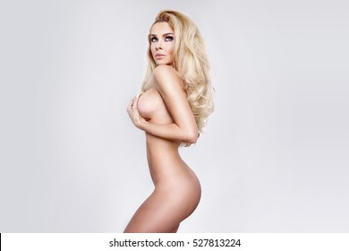 Beautiful sexy blonde model with a perfect body and your hair stands on a white background naked and undressed