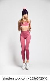 Beautiful sexy blonde with a perfect athletic slim figure, leads a healthy lifestyle, wears comfortable pink clothes in the style of sports. Warm hat with pompons