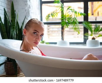 beautiful sexy blonde in red bikini takes a bath with sea salt and flowers, spa treatments