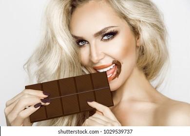 Beautiful, sexy blonde, sensually eating chocolate.