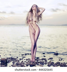 Beautiful sexy blonde stands on the seashore at sunrise