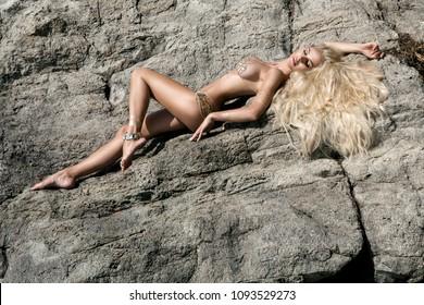 Beautiful, sexy blonde woman in bikini, sensual lingerie on the beach by the rocks.