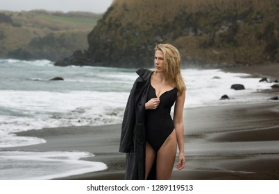 Beautiful and sexy blonde woman in black swimsuit with leather jacket at the beach.