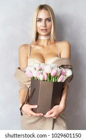Beautiful sexy blonde woman blue eyes in sexy beige lingerie with spring flowers bouquet light pink and white colored formed in gift box for you any celebrating