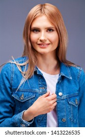Beautiful sexy blonde woman in blue denim jacket. Fashion model in jeans clothing. Isolated on gray studio