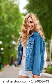 Beautiful sexy blonde woman dressed in a denim jacket and shorts. Fashion model in jeans clothing.  Summer Park outdoor