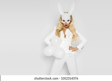 Beautiful, sexy blonde woman in elegant clothes in polka dots and in a white rabbit mask