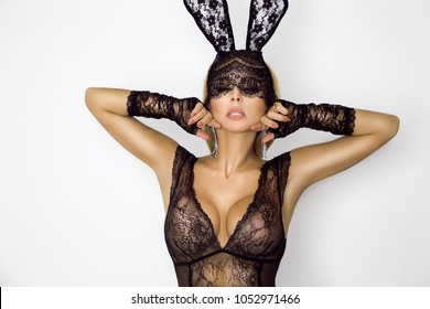 Beautiful, sexy blonde woman in elegant lingerie and black lace Easter bunny mask, standing on white background