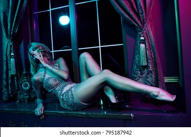 Beautiful sexy blonde woman lies on a window sill in the nightclub , glam party
