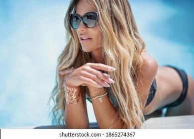Schöne sexy blonde Frau mit langen Haaren und gegerbtem Körper mit schwarzem Badeanzug und Sonnenbrille posiert am Schwimmbad.