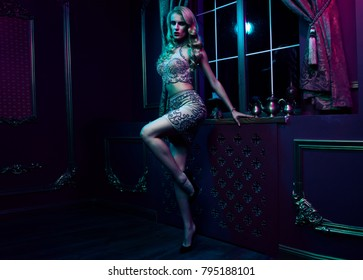 Beautiful sexy blonde woman on violet background, party.