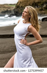 Beautiful sexy blonde woman poses in white long dress at a black sand beach in Azores.