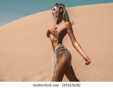 Beautiful sexy blonde  woman tanned skin face cosmetic makeup wear silver  accessories, diamonds on tan body, brilliants on face, sand color safari summer casual, walking in the sand of desert dunes