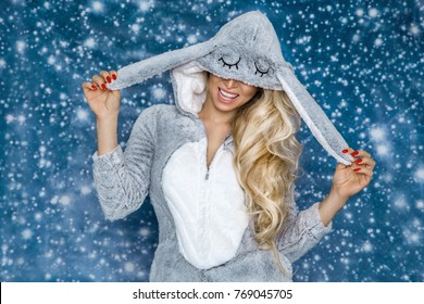 Beautiful sexy blonde woman wearing a pajama, a bunny costume, smiling happily. Fashion model on a winter background.