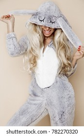 Beautiful sexy blonde woman wearing a pajama, a bunny costume, smiling happily. Fashion model on a beige background in  Easter bunny costume.