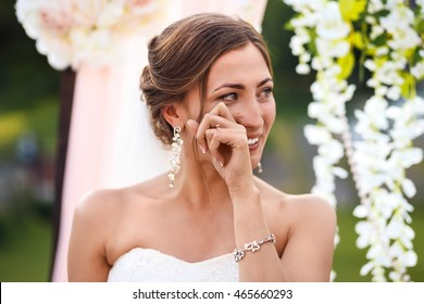 Beautiful sexy bride in white dress weeps.  tears of happiness on the wedding day.