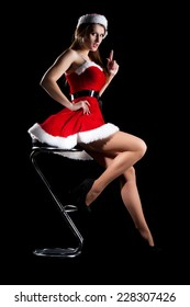 Beautiful sexy brunette girl in a Christmas suit posing on a black background