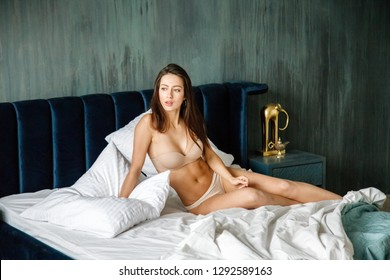 Beautiful sexy brunette girl in lingerie lying in bed