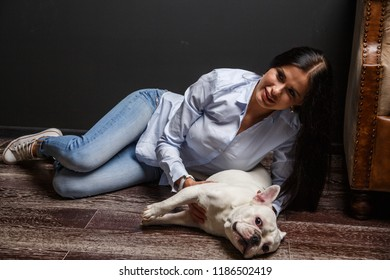 Beautiful sexy brunette girl posing with a dog in the interior