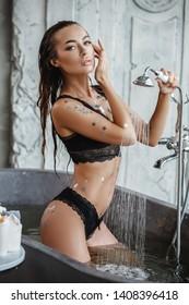Beautiful sexy brunette girl posing around the bathroom and bathing
