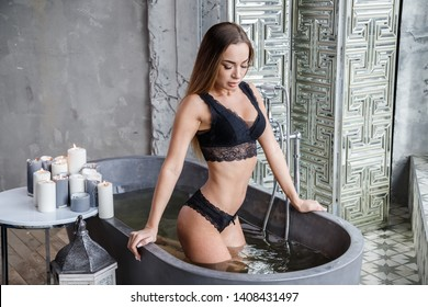 Beautiful sexy brunette girl posing around the bathroom and bathing