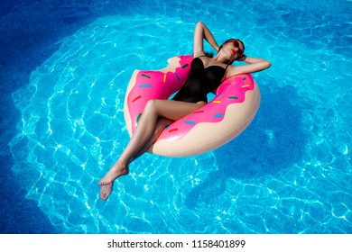 Beautiful sexy brunette girl in swimming pool on inflatable circle